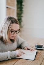 a woman sitting reading a Bible