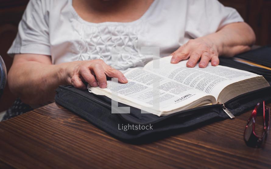 elderly woman reading a Bible
