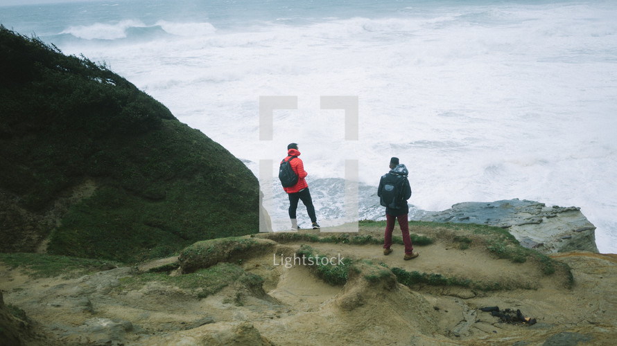 men with backpacks standing at the edge of a cliff