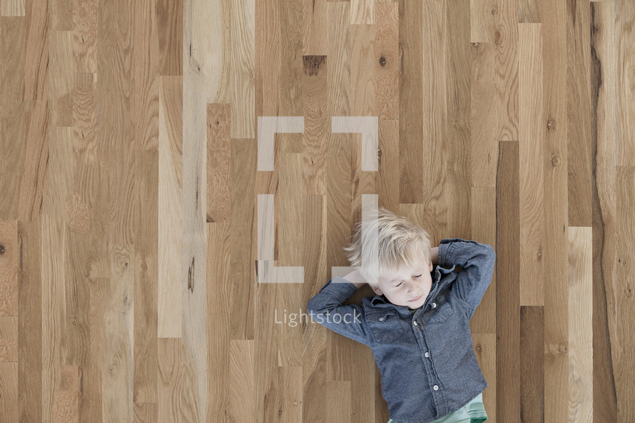 A toddler boy lying on a wood floor with his eyes closed.