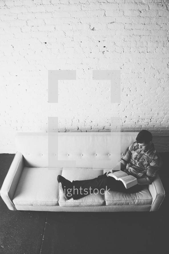 man reading a Bible on a couch