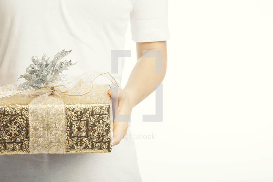 A man holding out a gold and silver wrapped gift with a bow