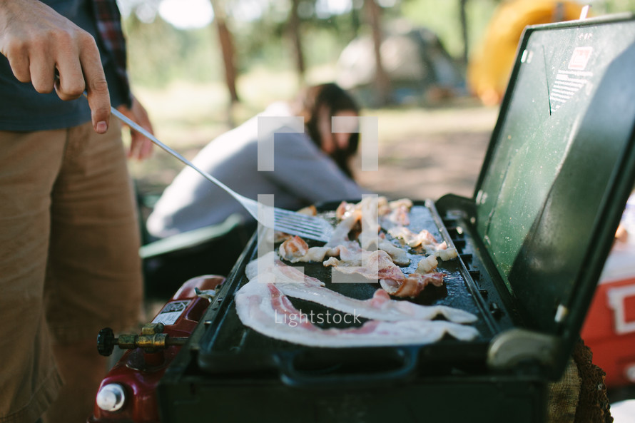a man flipping bacon on a camping grill