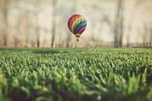 hot air balloon landing in the green grass