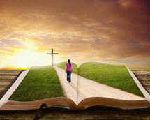 woman walking on a path towards the cross on a Bible