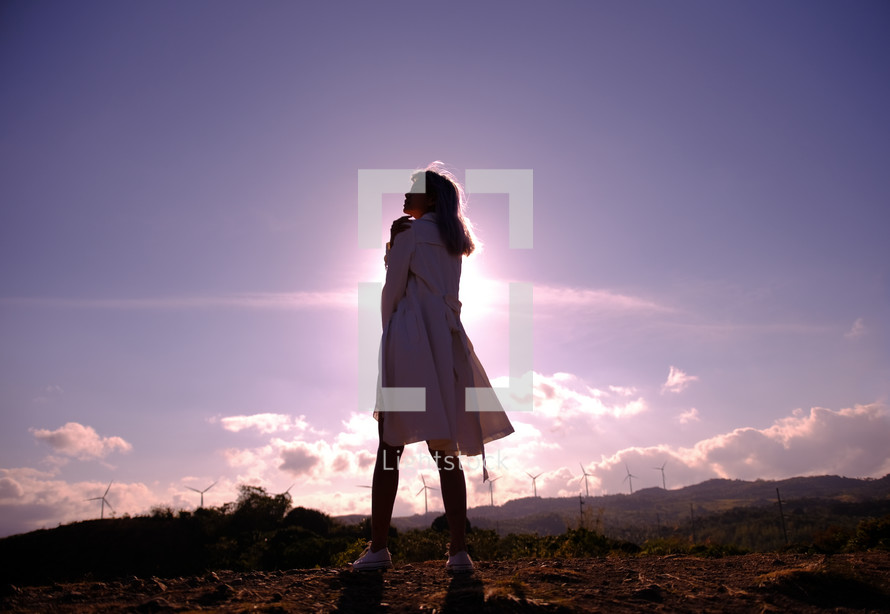 a woman standing outdoors with distant wind turbines