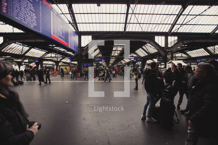 people walking through a train station