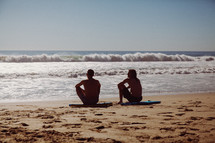 guys sitting on boogie boards in the sand on a beach