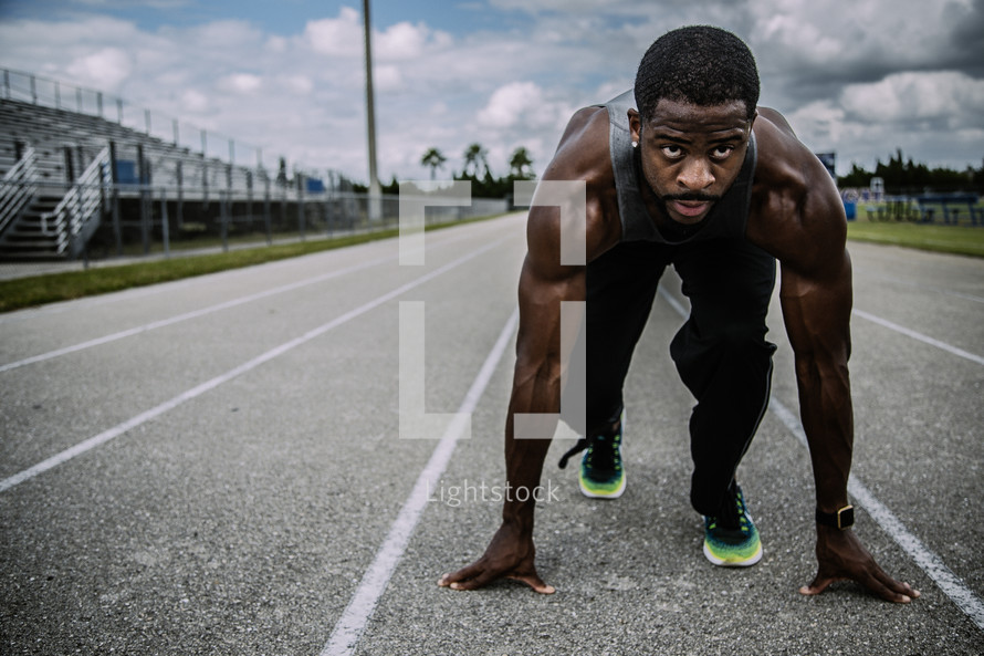 a man in a runner's stance on a track