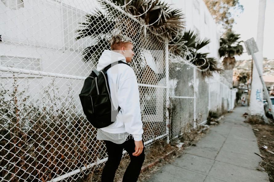 teen boy walking down a sidewalk