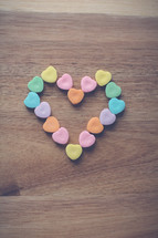 heart shaped candy in the shape of a heart on wood