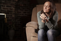 woman in prayer inside her home.
