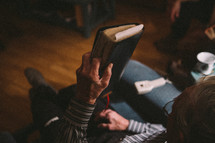 A man sits in a lounge chair holding a Bible.