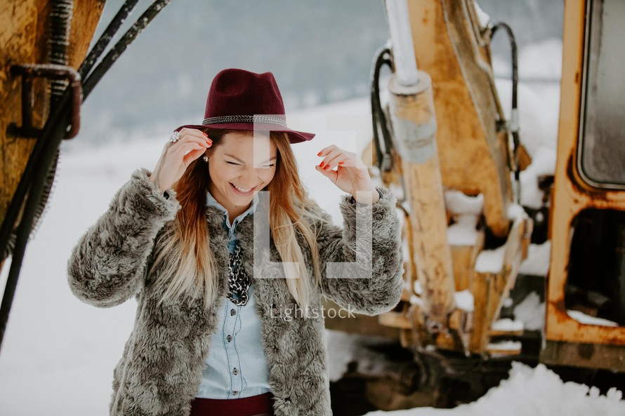 a woman in a fur coat standing under a backhoe in snow