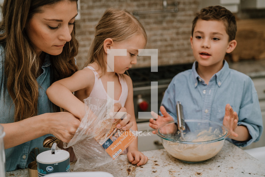 a mother baking cookies with her children