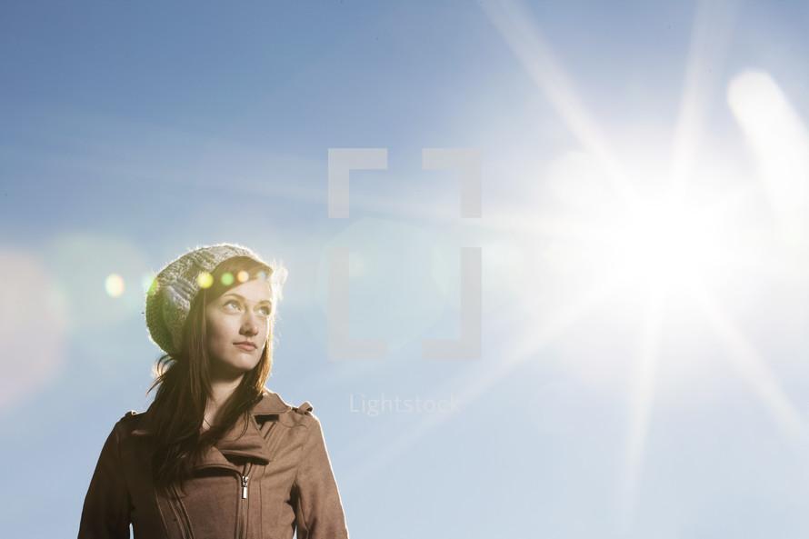 Teenage girl looking toward the sun.