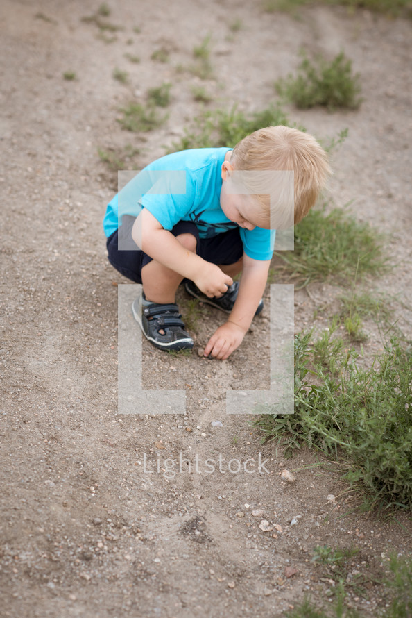 a toddler boy playing in sand