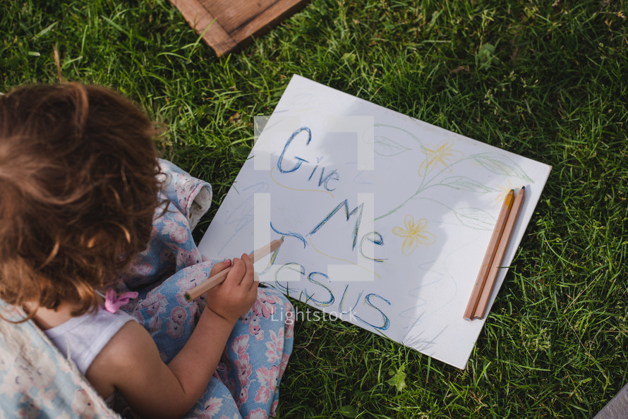 a child drawing a give me Jesus sign