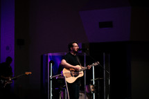 a man singing with a guitar during a worship service
