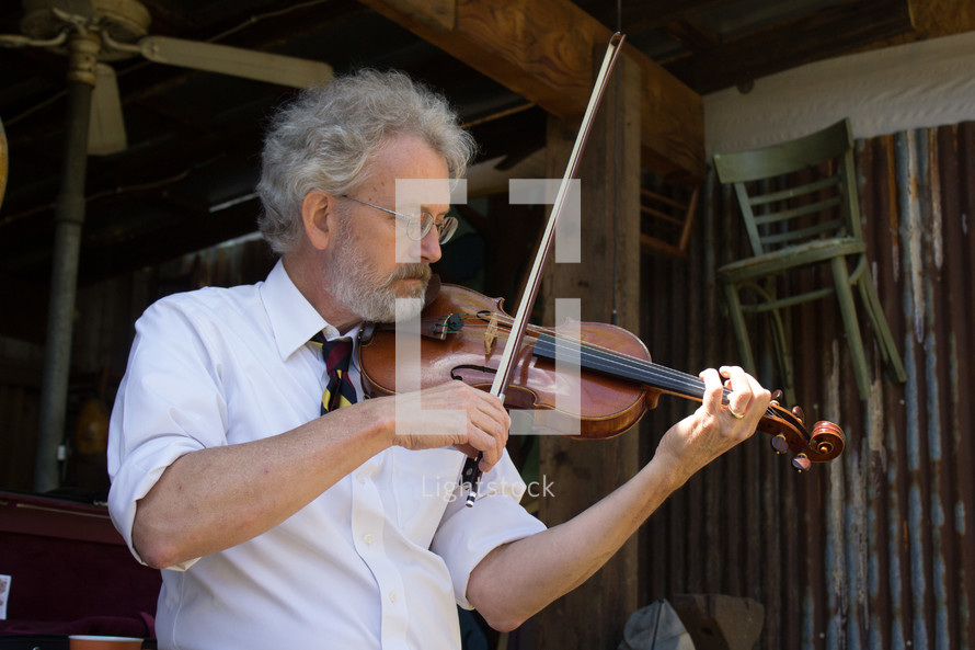 a man standing in a barn playing a fiddle