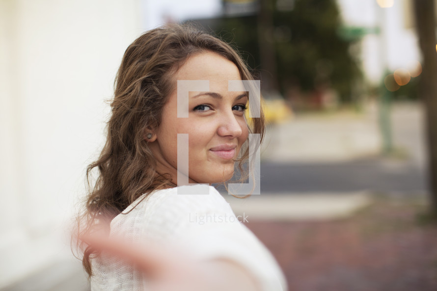 a young woman gesturing to come this way