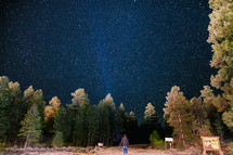 a man with a flashlight looking up at stars in the night sky