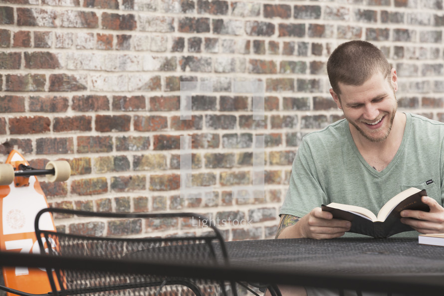 man reading a Bible outdoors at a table