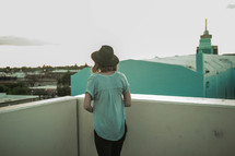 a woman standing on a rooftop looking over a railing