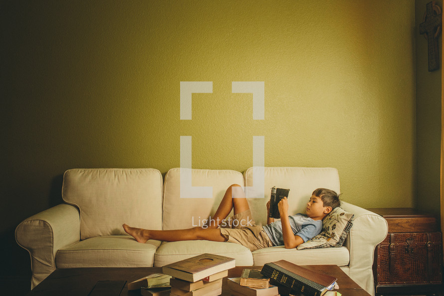 Boy reading the Bible while laying on the couch.