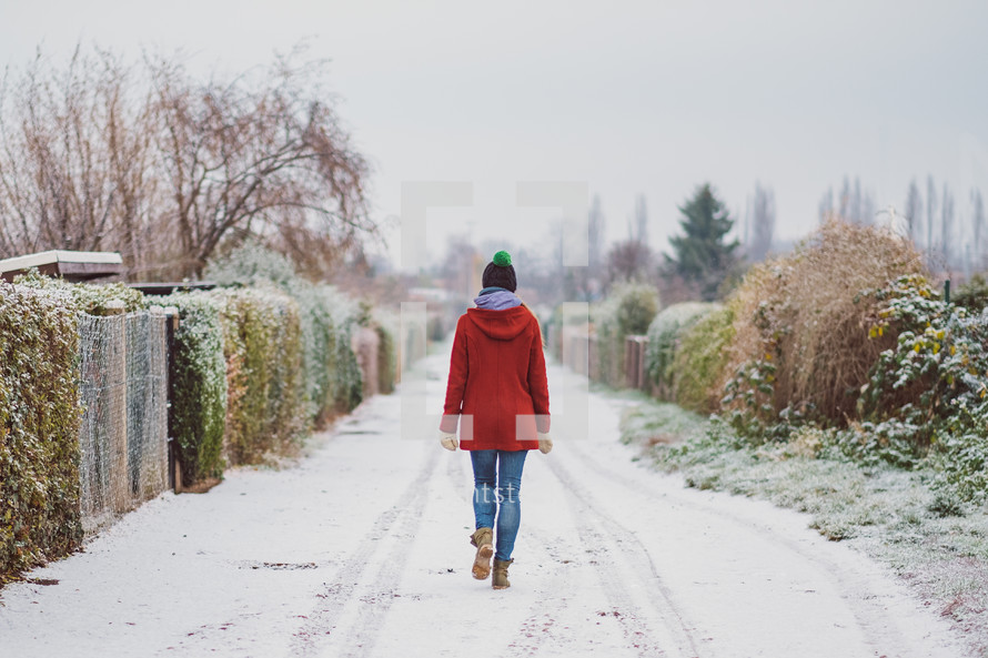 a woman walking on a snow covered road