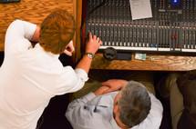 two men working a soundboard