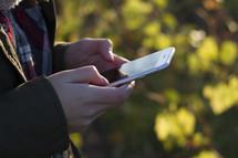 Millennial sending a text message outdoors in the fall.