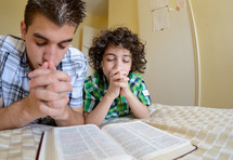Two brothers praying over Bible at bedtime.