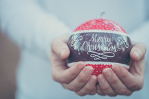 an large red ornament with the words Merry Christmas in a man's hands