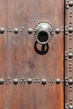 Pull ring on an ancient wooden door with rivets.