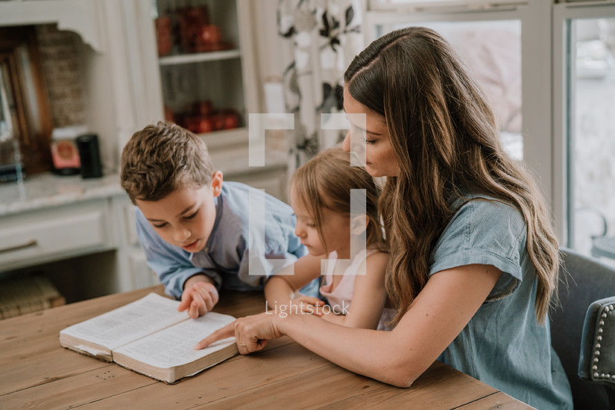 a mother reading a Bible with her children