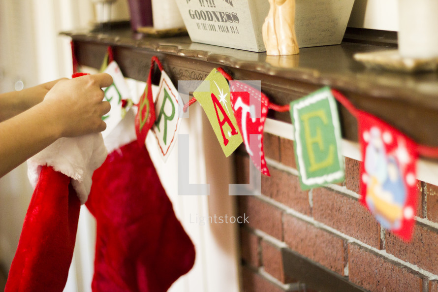 Hanging stockings on the fireplace mantle.