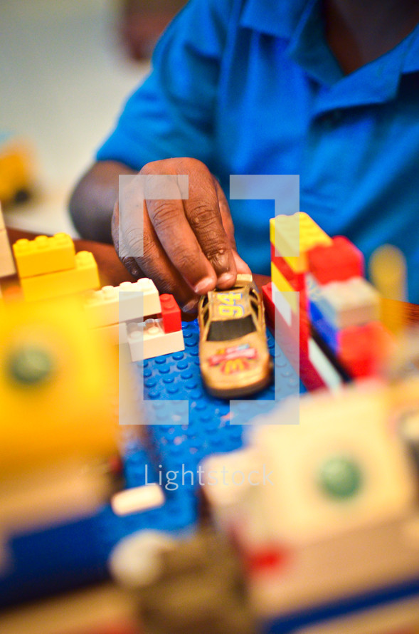 boy child playing with legos and a toy car