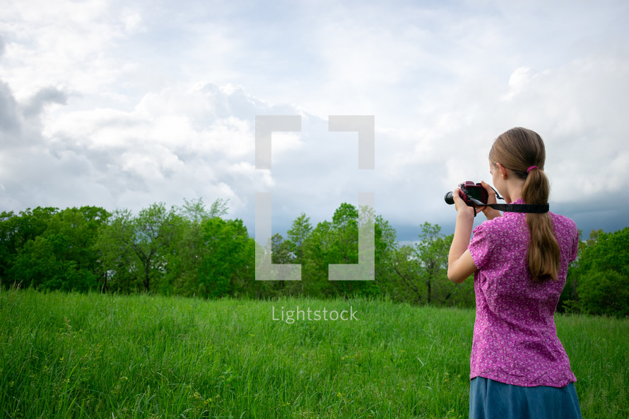 a girl holding a camera taking pictures