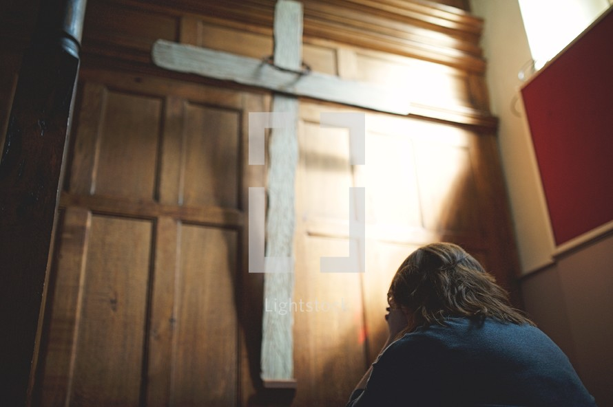a woman covering her face in shame praying in front of a cross in a church