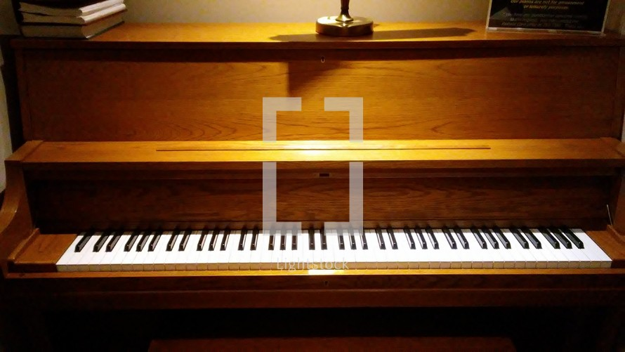 A closeup view of the piano keys and wooden body of a Church piano lit in an church sanctuary.
