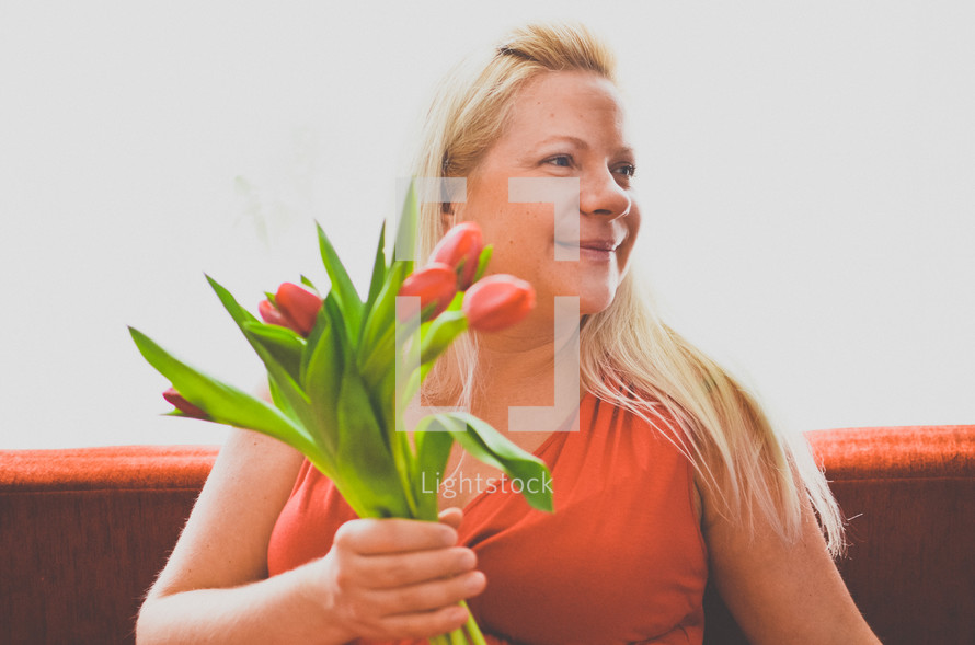 a pregnant woman holding tulips