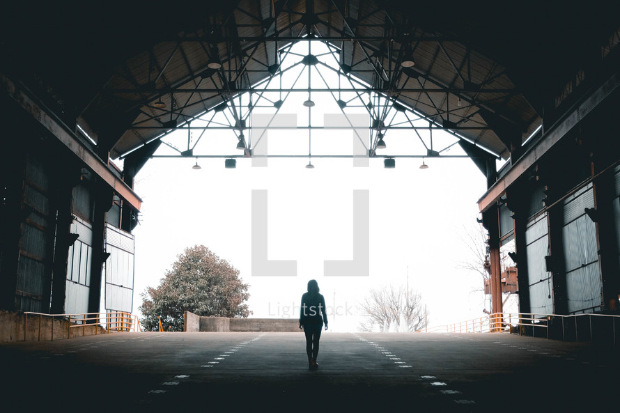 a woman standing under a covered roof looking out at the fog