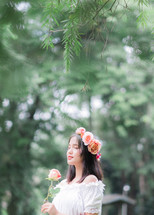 girl holding a rose with flowers in her hair