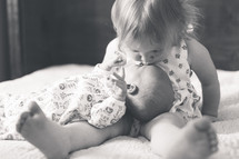a toddler girl kissing her baby sister