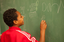 child writing on a classroom chalkboard