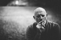 A bald man smoking a cigar