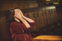 a woman covering her face sitting alone in a church