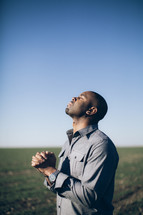 man in prayer with his head lifted towards God