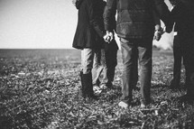 group holding hands in prayer in a field